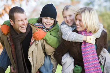 Parents outdoors piggybacking two young children and smiling