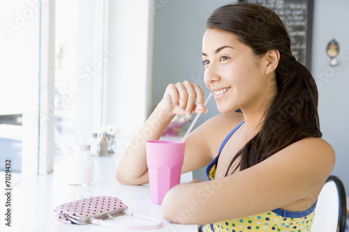 Young woman having cold drink in cafe