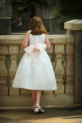 little flower girl at wedding trying to see the bride