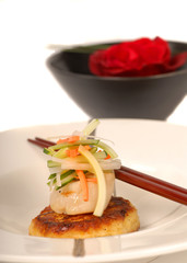 Asian crabcake and scallop appetizer with rose in background