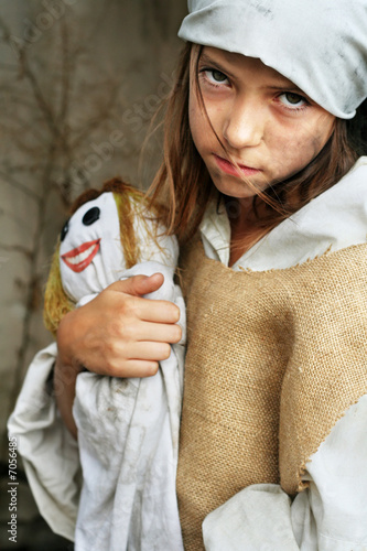 Sad, poor, dirty child holding a smiling doll.