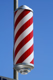 striped barbers pole set against bright blue sky poster