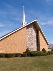 modern rural brick church by a grass lawn