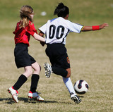 Two youth soccer girls compete for the ball poster