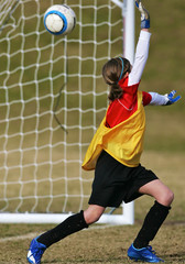 Girls youth socer goalie misses a shot on goal