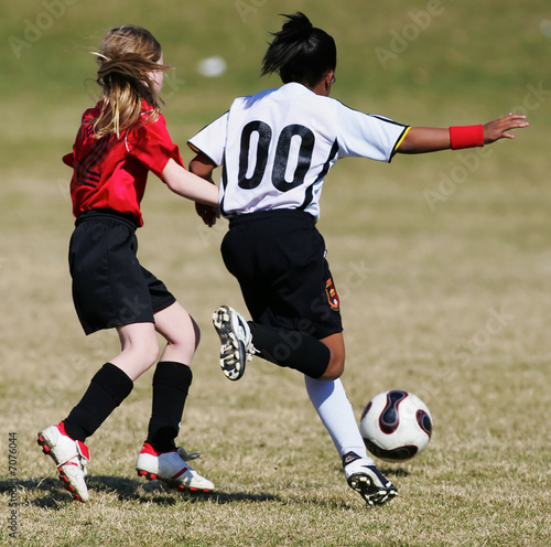 Two youth soccer girls compete for the ball