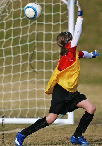 Girls youth socer goalie misses a shot on goal
