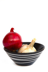 Red onion and garlic in a black bowl with white pattern