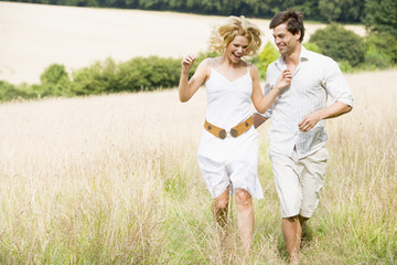 Couple running through summer field