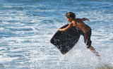 Young child in the air on his boogie board