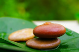 Small river stones in balance on a leaf,(droplet is sharp) poster