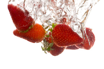 Mehrere Erdbeeren fallen in Wasser und machen Luftblasen
