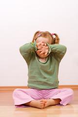 Little girl hiding behind her hands - copyspace