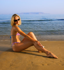 Beautiful young woman shaving her legs on a beach