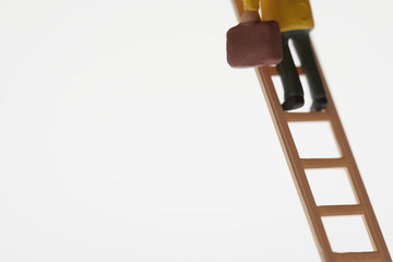 Businessman figurine climbing ladder, low section