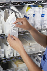 Nurse at shelves with medical supply, close-up of hands