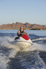 Young man riding jetski on lake