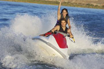 Young couple riding jetski on lake