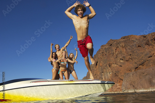 Young man jumping from boat, friends watching in background