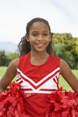Girl cheerleader 7-9 years standing on soccer field, portrait