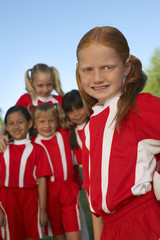 Group of girl soccer players 7-9 years standing on field, portrait