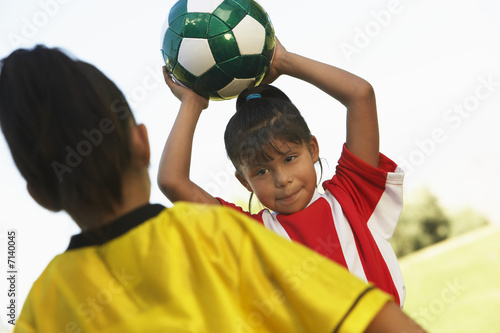 Girl soccer player 7-9 years preparing to throw ball