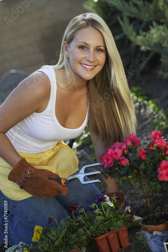 Woman gardening, smiling, portrait