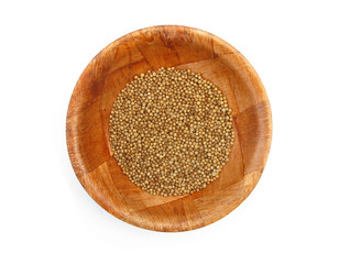 Coriander dried seeds spice in wooden dish isolated
