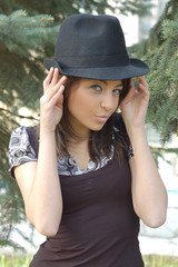 Beautiful girl holding hat