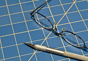 Stainless steel razor knife and glasses on a blue cutting mat