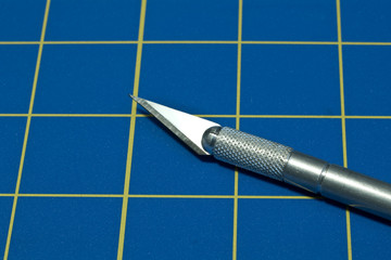 Stainless steel razor knife on a blue cutting knife