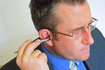 Business man at work with pen in his ear