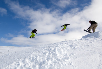 Snowboarders Jumping