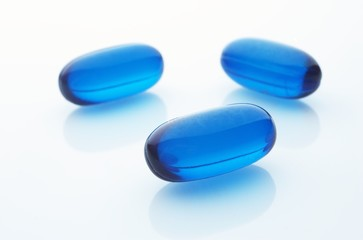 Three blue capsules on white background