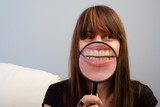 Amused young woman concept.  Girl and magnifier on mouth poster