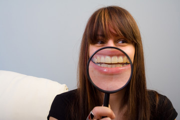 Amused young woman concept.  Girl and magnifier on mouth