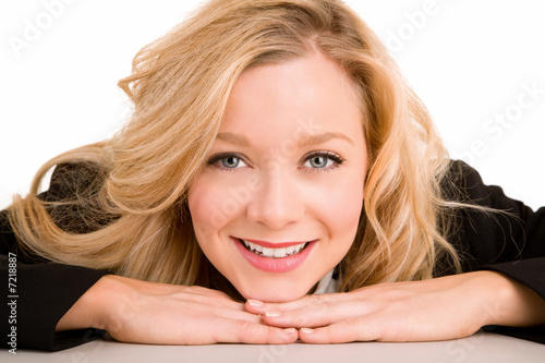 A beautiful smiling woman is laying on her desk