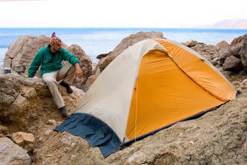 Man near a tent ashore sea