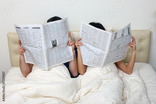 Couple reading newspapers