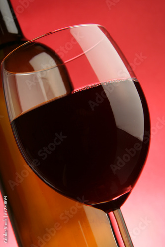 Glass and bottle of red wine close-up