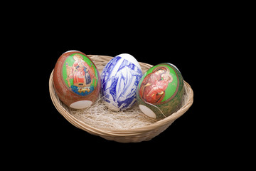 Easter eggs in a basket on the isolated black background
