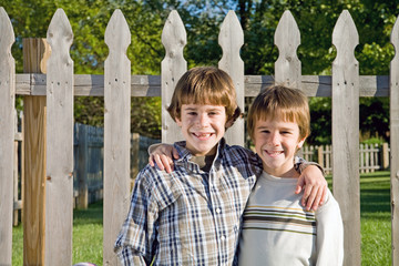 Two Brothers In Front of Fence