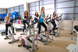 Women working out on spinning bikes at the gym