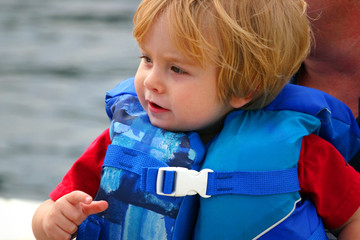 toddler in lifejacket on boat