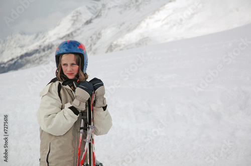 portrait of girl in snowy mountains holding skis