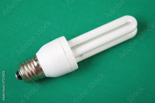 energy-saving lamp on green background