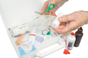 First aid kit and hands with gloves cutting the bandage