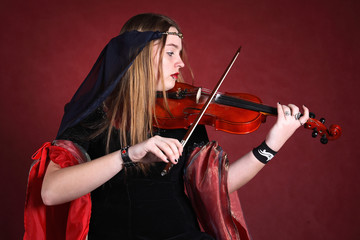 beautiful girl in an ancient dress plays on a violin