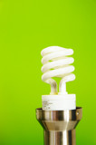 Compact fl light bulb, on green background (green power)