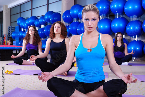 Beautiful girls meditating in fitness club